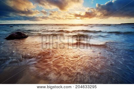Seascape at sunset with rainy clous on the horizon