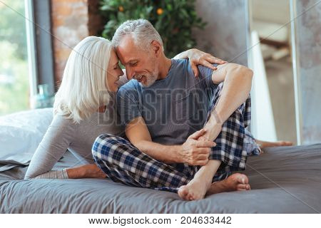 True love. Pleasant aged loving couple sitting on the bed forehead to forehead and expressing their feelings while resting in the bedroom