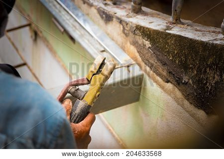 hand hold of elderly welder works steel welding repair on roof high. select focus with shallow depth of field