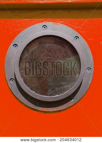 close up of rusty metal vintage porthole on a red wooden boat with screws in summer light