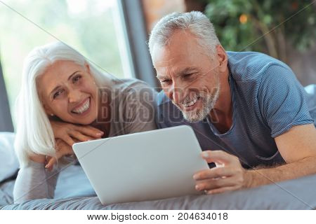 Pleasant leisure time. Cheerful handsome elderly man using laptop and smiling while lying in bed with his wife