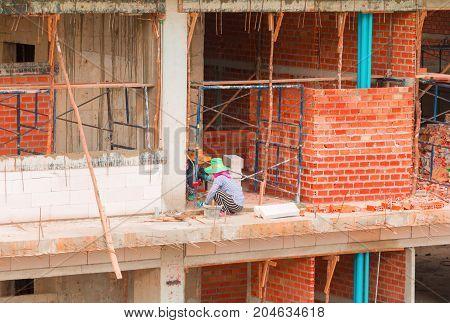 Bricklayer Female worker work industrial installing wall bricks in construction site