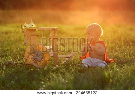 Little boy king sits with a horse toys outdoors at sunset with the light beam. Prince eats resting on the grass.
