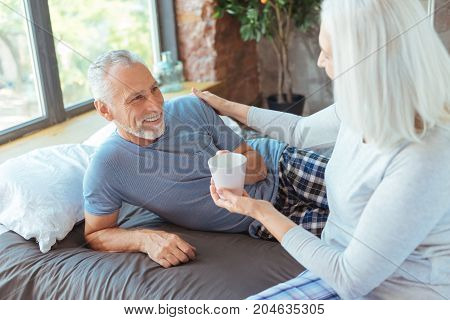 Sign of love. Pleasant loving aged woman holding a cup of coffee and bringing it to her smiling husband while taking care of him in the background