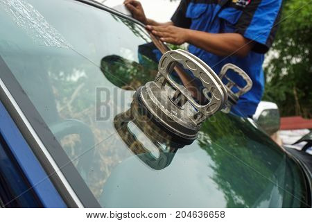 Glazier using tools repairing to fix crack broken windshield on the front window glass of the machine car accident.