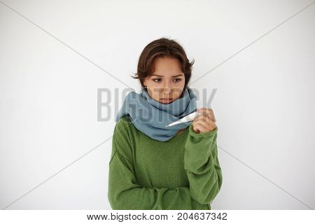 Isolated portrait of unhappy frustrated young Hispanic female wearing warm sweater and scarf around her neck looking at thermometer in her hands while running high temperature feeling sick