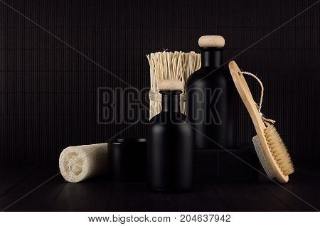 Noir exquisite bathroom decor with blank black cosmetics bottles bath accessories on dark wood board mock up. Template for advertising designers branding identity cover.