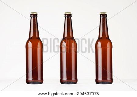 Three brown longneck beer bottles mock up. Template on white wood table.