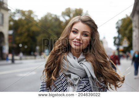 Outdoor picture of happy stylish woman traveler with long wavy hair enjoying nice walk in European city looking and smiling cheerfully at camera. Youth joy moments of carefree and true happiness