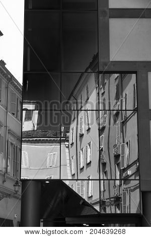 Parma (Emilia Romagna Italy): old and modern buildings in the Cesare Battisti square. Reflections. Black and white
