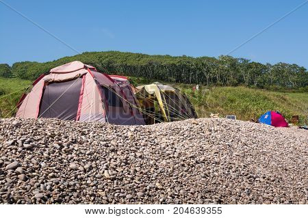 Camping containing two tents and located on pebble shore. There is a hill overgrown by grass and trees behind it.
