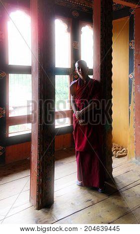 Punakha, Bhutan - September 10, 2016: Young Novice Buddhist Monk In Reddish Orange Robes Standing In