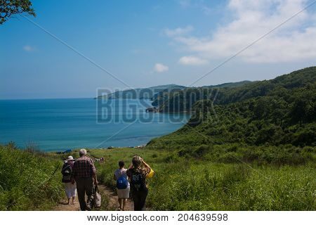 People tourist walking down to the sea coast. Coast framed by green hills.