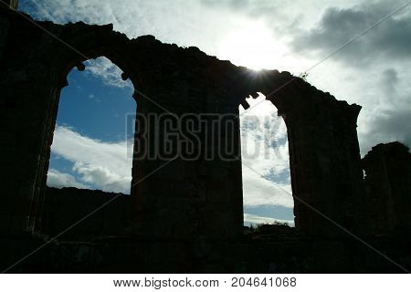 A ruined abbey in Basingstoke silhouetted by the sun
