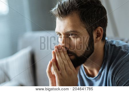Difficult times. Cheerless nice handsome man holding his hands together and thinking about his problem while feeling depressed