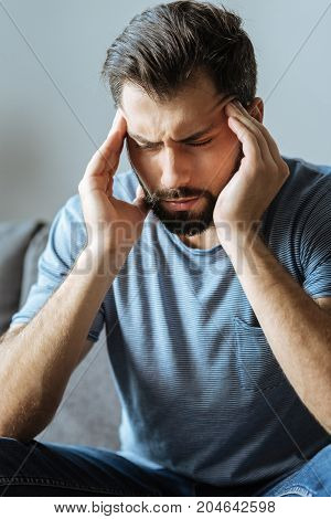 Awful headache. Depressed nice good looking man holding his temples and closing eyes while having an awful headache