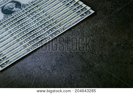 One dollar banknotes on a black table. Cash money american dollars. Vintage background. Lens flare. American currency.
