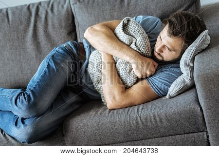 Feeling of solitude. Depressed cheerless nice man lying on the sofa and holding a cushion while feeling lonely