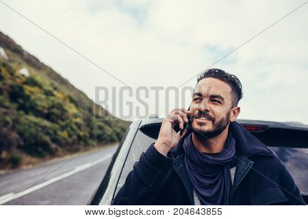 Handsome young man standing outdoors near his car and talking on the mobile phone. Young man on road trip making a phone call.