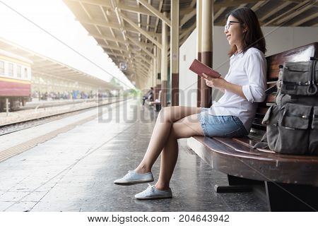 Asian Female backpacker is sitting at Thai train station. Young Woman is reading on her diary. Enjoying travel.