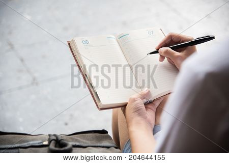 Close up woman backpacker hands writing notes in diary.
