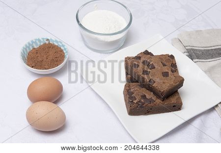 Chocolate brownie slices on a white plate with eggs, flour and coco powder