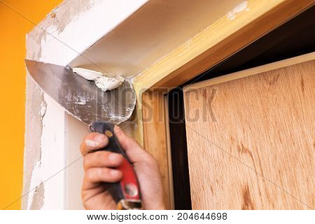 patching plaster around a new door reveals with spatula