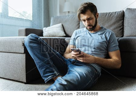 Nothing new. Sad handsome cheerless man sitting on the floor and checking messages on his smartphone while feeling lonely