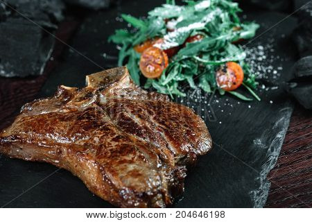 Grilled T-bone steak with tomatoes and spices on dark background