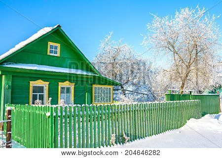 rural wooden house in winter covered with snow. a frost wintry day. green wooden home in village. rustic winter landscape
