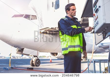 Low angle side view serious airport staff controlling tool while standing near big plane