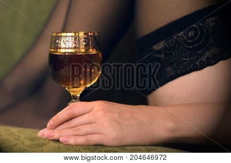 Sexy woman in black stockings drinking wine on sofa close up. Female legs in stockings.