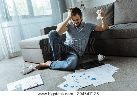 Where is solution. Unhappy stressed out handsome man sitting on the floor and looking for a solution to the problem while working at home
