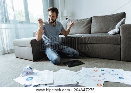 In despair. Angry unhappy desperate man sitting on his knees and crumbling paper while being in despair