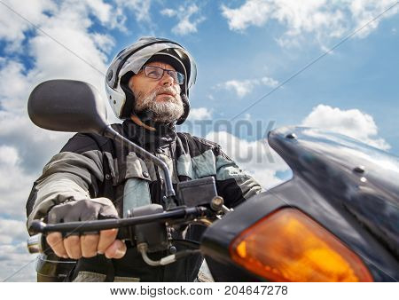 elderly motorcyclist wearing a jacket and glasses with a helmet sitting on his motorcycle on the road closeup