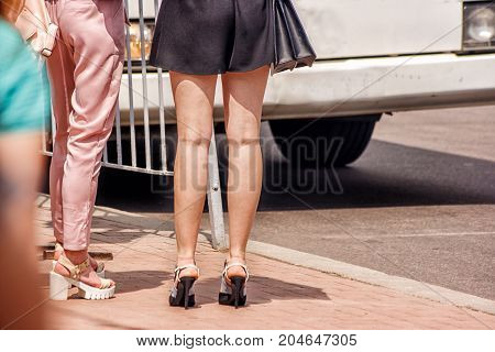 women is waiting to cross the road on sunny summer day