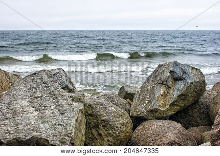 sea waves break down on a large stone on overcast summer day