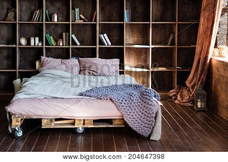 Modern bedroom in a loft. Urban apartment with pallet bed, scandinavian eco design
