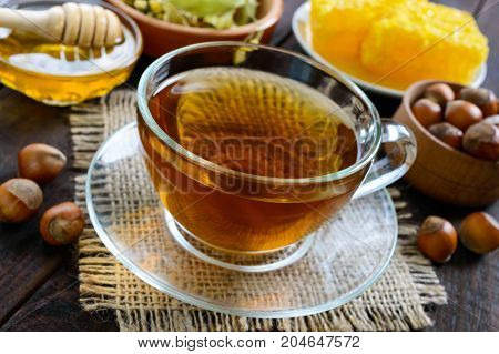 A cup of fresh fragrant herbal tea with honey and hazelnuts on a dark wooden background. Close-up.
