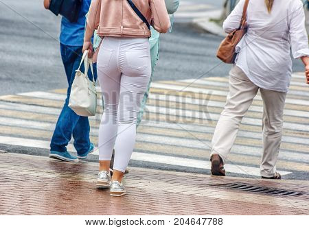 legs of the people going on the street on sunny summer day