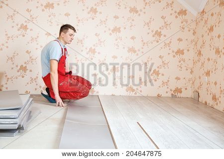 handyman laying down laminate flooring boards while renovating a house
