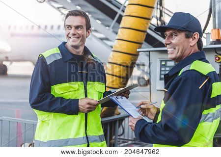 Portrait of beaming male standing near cheerful colleague. They filling documents