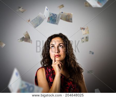 Girl and falling Euro banknotes. Currency and lottery concept. Young woman is doing something.