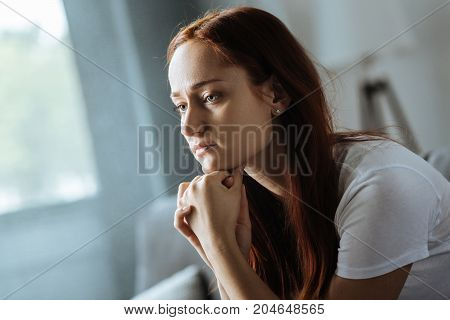 Unhappy thoughts. Serious gloomy pretty woman holding her chin and thinking about her problems while being at home