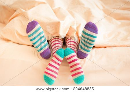 Couple in Christmas socks in bedroom. Man and woman lying on bed. People relaxing at home. Winter holiday Valentine day concept