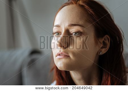 Chronic condition. Sad moody red haired woman sitting at home and thinking about her problems while suffering from depression