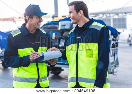 Cheerful mechanic telling with outgoing colleague. He writing notes on paper at airport during job