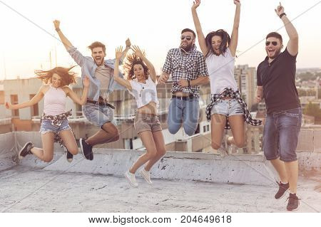 Group of young people having fun at a rooftop party jumping. Focus on the people in the middle