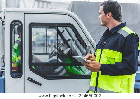Side view smiling male mechanic making notes in electronic tablets while looking on car. Man in uniform driving it at airport