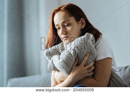 I am lonely. Sad depressed attractive woman hugging a cushion and thinking about her life while feeling lonely